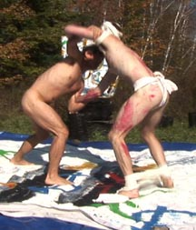 Two men wreslting - one bound and blindfolrded, the other naked